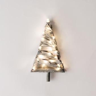Minimalistische kerstboom met lampjes op een lichte achtergrond. nieuwjaar aard minimaal concept.