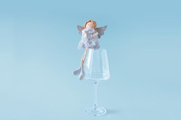 Minimalistische kerstsamenstelling. zachte engel zit op groot transparant wijnglas op blauwe achtergrond.