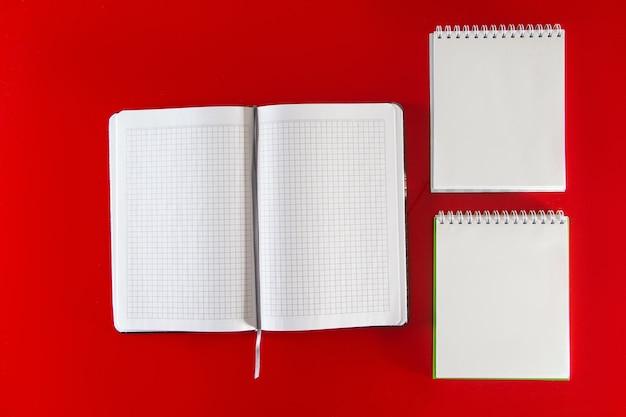 Minimalistische lay-out voor ontwerp kantoorbenodigdheden notebooks en pennen op een rode achtergrond