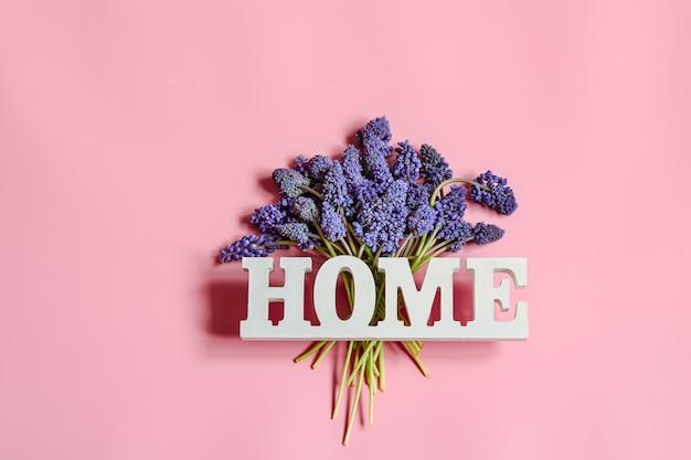 Minimalistische lentecompositie met blauwe bloemen en het decoratieve woord home.
