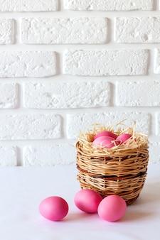 Minimalistische pasen-compositie met rieten mand en roze gekleurde eieren op witte ondergrond