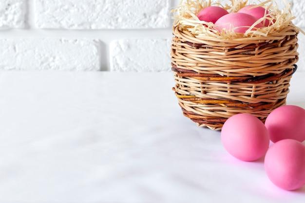 Minimalistische pasen-samenstelling met rieten mand en roze gekleurde eieren op witte achtergrond. kopieer ruimte