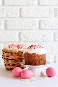 Minimalistische pasen-samenstelling met rieten mand met roze gekleurde eieren en pasen-cake op witte oppervlakte