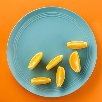 Minimalistische plakjes sinaasappel op een blauwe plaat