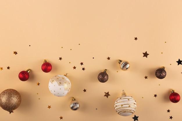 Minimalistische ronde witte rode en gouden kerstballen op een neutrale achtergrond met sterren bovenaanzicht en kopieer de ruimte