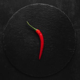 Minimalistische roodgloeiende chilipeper op donkere achtergrond