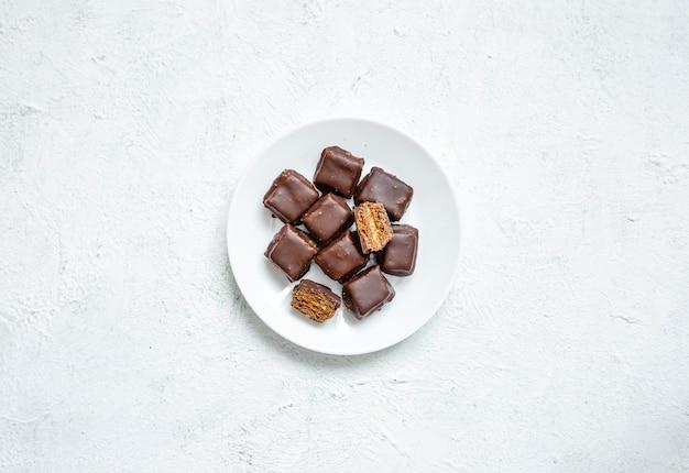 Minimalistische samenstelling van cookies in chocoladesuikerglazuur in een witte plaat.