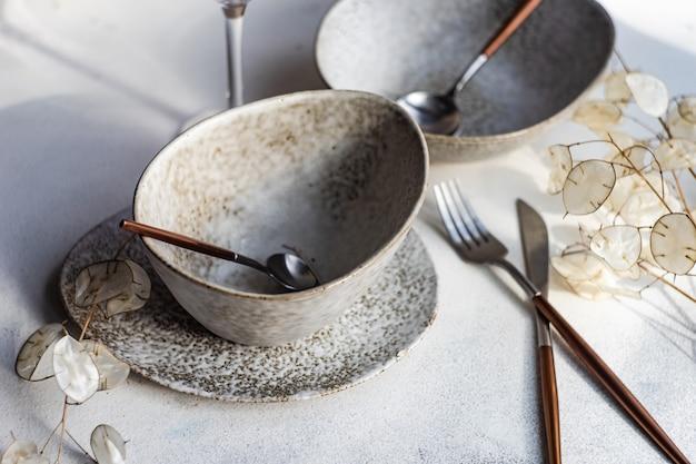 Minimalistische tafelsetting in pastelkleuren op wit beton