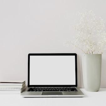 Minimalistische thuiskantoor-werkruimte met laptop, bloemenboeket op roze