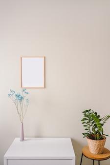 Minimalistische vrouwelijke stilleven werkplek interieur pastelkleuren. witte tafel, lege poster mock-up frame, stijlvolle roze poeder vaas met blauwe droge bloemen