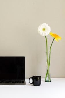 Minimalistische werkplek met laptop en bloemen in glazen vaas op bureau