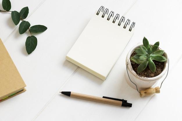 Minimalistische werkruimte met notitieblok en pen en kamerplantvaas