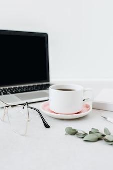 Minimalistische werkruimte voor thuiskantoor. laptop, koffie, bril, notitieboekje, eucalyptus