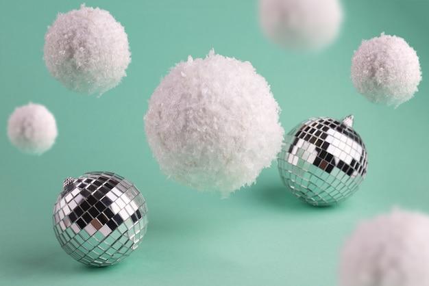 Minimalistische wintersamenstelling met big flying snowballs en en disco ball.