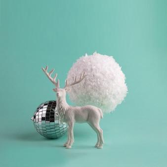 Minimalistische wintersamenstelling met white deer en grote decoratieve sneeuwbal.