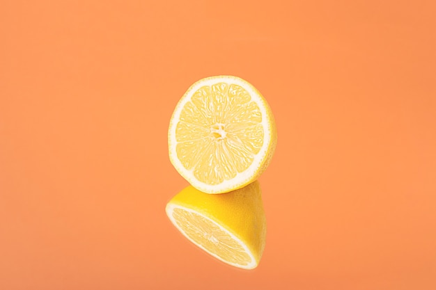 Minimalistische zomerfruit tropische compositie. de helft van sappige verse citroen met spiegelbeeld op fel oranje achtergrond. ruimte kopiëren
