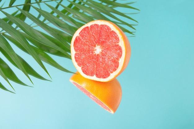 Minimalistische zomerfruit tropische compositie. de helft van sappige verse grapefruit en palmbladeren met spiegelbeeld op blauwe achtergrond. ruimte kopiëren.