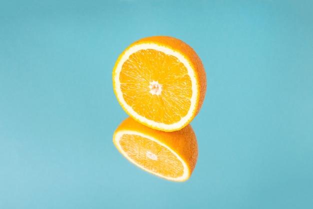 Minimalistische zomerfruit tropische compositie. de helft van sappige verse sinaasappel met spiegelbeeld op blauwe achtergrond. ruimte kopiëren