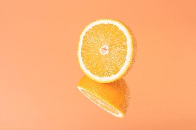 Minimalistische zomerfruit tropische compositie. de helft van sappige verse sinaasappel met spiegelbeeld op fel oranje achtergrond. ruimte kopiëren.
