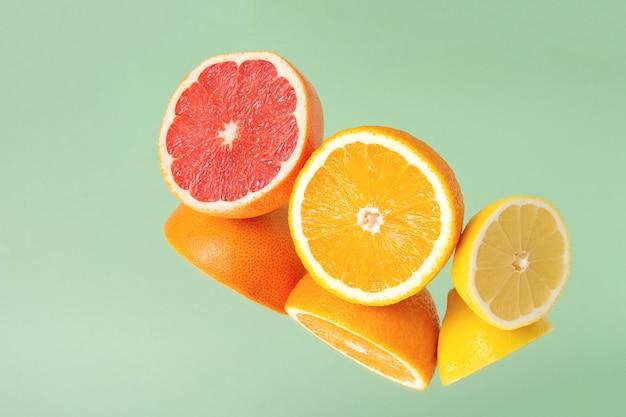 Minimalistische zomerfruit tropische compositie. helften van sappige verse sinaasappel, citroen en grapefruit met spiegelbeeld geïsoleerd op lichtgroene achtergrond. ruimte kopiëren.