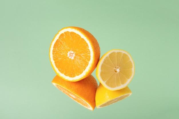 Minimalistische zomerfruit tropische compositie. helften van sappige verse sinaasappel en citroen met spiegelbeeld geïsoleerd op lichtgroene achtergrond. ruimte kopiëren.