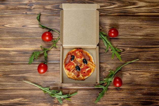 Minipizza die door een kind met tomaten, olijven en ham op een houten achtergrond wordt voorbereid