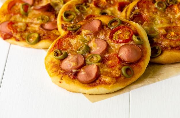 Minipizza met worsten en tomaten op een lichte achtergrond