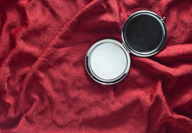 Minispiegel op een rode zijdeachtergrond. items uit de cosmetische tas voor dames. bovenaanzicht