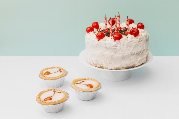 Minitaartjes en verfraaide cake op caketribune tegen dubbele achtergrond