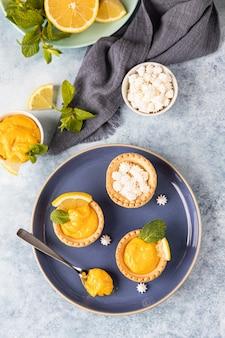 Minitaartjes met lemon curd, mini meringue, schijfjes citroen en munt op blauwe betonnen ondergrond