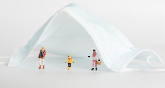 Miniture-familiemensen doen sociale afstanden onder chirurgische mas op een witte achtergrond, dankzij het pandemische coronavirus (covid-19) -slijtagemasker kan het leven conceptueel redden.