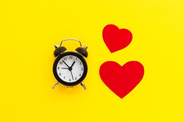 Miniwekker en rode harten op geel. tijd voor liefde en groeten. plat leggen. liefde in de lucht.