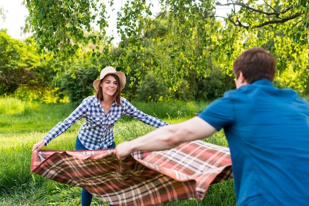 Minnaars die picknickdeken van aard zetten