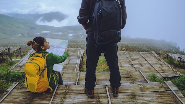 Minnaarvrouw en -mannen reizen ontspannen in de vakantie. bekijk kaart verken de bergen
