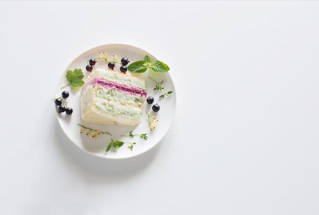 Mint cheesecake met zwarte bessen op plaat op witte tafel