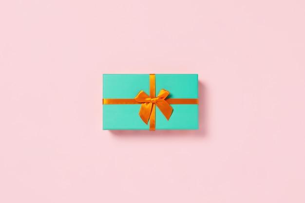 Mint geschenkdoos op een roze tafel.
