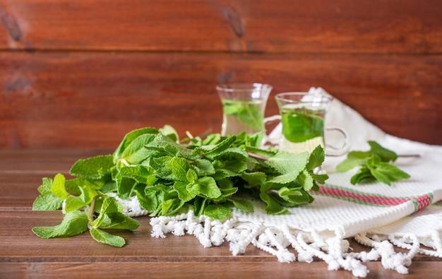 Mint liefs met 2 kleine glazen theekopjes op achtergrond op houten tafel