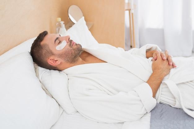Minuut om te ontspannen. goed uitziende aantrekkelijke man met ooglapjes terwijl u ontspant op het bed