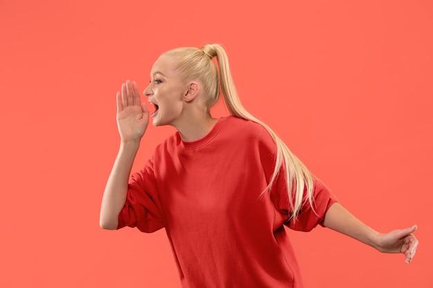 Mis niet. jonge casual vrouw schreeuwen. roepen. huilende emotionele vrouw die op de achtergrond van de koraalstudio gilt. vrouwelijk portret van halve lengte. menselijke emoties, gezichtsuitdrukking concept. trendy kleuren