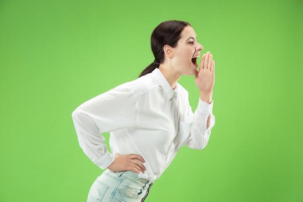 Mis niet. jonge casual vrouw schreeuwen. roepen. huilende emotionele vrouw die op groene studioachtergrond gilt. vrouwelijk portret van halve lengte. menselijke emoties, gezichtsuitdrukking concept. trendy kleuren