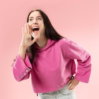 Mis niet. jonge casual vrouw schreeuwen. roepen. huilende emotionele vrouw die op roze studioachtergrond gilt. vrouwelijke halve lengte portret. menselijke emoties, gezichtsuitdrukking concept. trendy kleuren