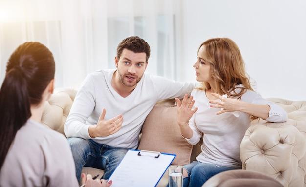 Miscommunicatie tussen mensen. emotionele ongezellig jonge man en vrouw zittend op de bank en gebaren terwijl ze het niet met elkaar eens zijn