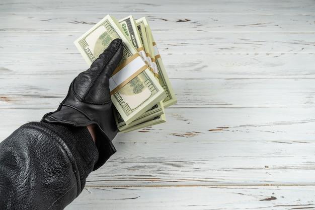Misdaad concept man in zwart lederen handschoenen bedrijf bakstenen van geld