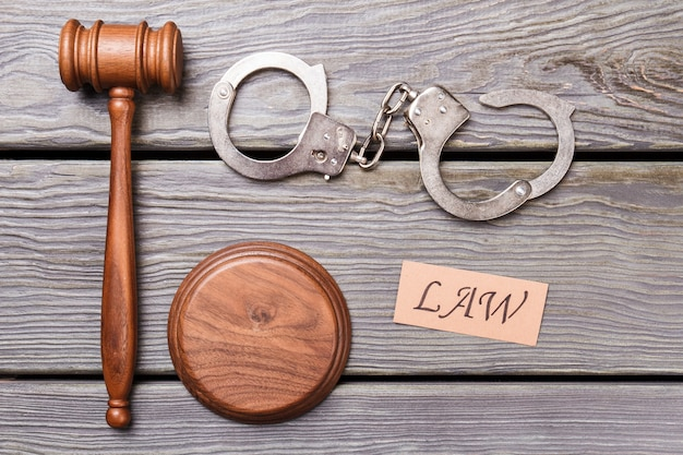 Misdaad en recht concept. houten hamer met handboeien op houten bureau.