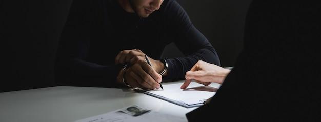Misdadige mens met handboeien die document in ondervragingsruimte ondertekenen