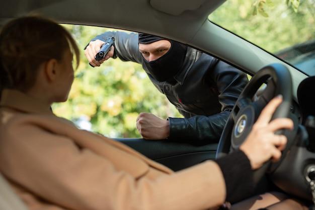 Misdadiger in zwart masker bedreigt een vrouw met een pistool tijdens het autorijden