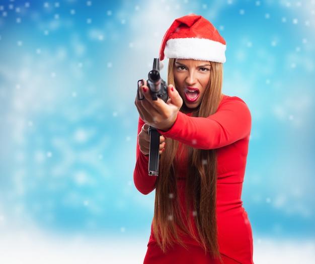 Misdadiger met kerstmuts en een pistool