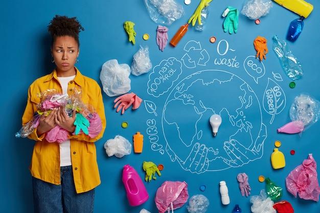 Miserabele, donkere milieuactivist poseert met plastic afval, raapt afval op, boos als het leven op een vervuilde planeet, poseert tegen een blauwe achtergrond.