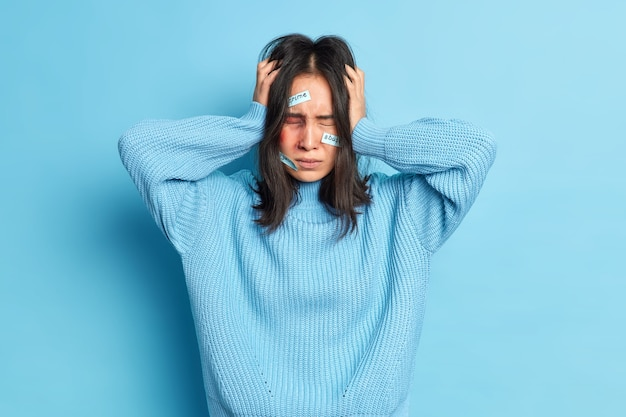 Mishandelde geslagen jonge vrouw houdt handen op haar hoofd lijdt aan ernstige hoofdpijn wordt slachtoffer van agressieve echtgenoot heeft gekneusd gezicht gekleed in trui