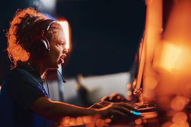 Mislukking zijaanzicht van boos gemengd ras meisje vrouwelijke cybersport gamer die een koptelefoon draagt, voelt zich overstuur